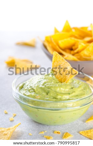 Traditional mexican homemade guacamole sauce in a glass bowl and a bowl with tortilla chips on a light stone background. Party food concept.  Front view, copy space, vertical image, high key