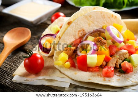Traditional Mexican tortilla bread stuffed with meat and vegetables on the table.Selective focus on the front tortilla - stock photo