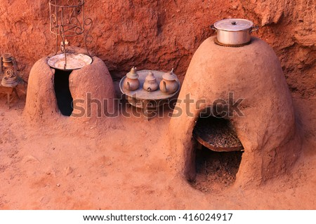 Traditional Moroccan earth ovens made out of sandstone with a pot cooking food  and tea kettles