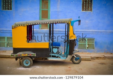 Traditional motorized rickshaw against a blue wall in Jodhpur, Rajasthan, India - stock photo