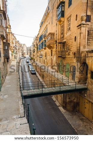Traditional narrow street, old houses and footbridge in Malta. Maltese architecture in Valletta, Malta - stock photo