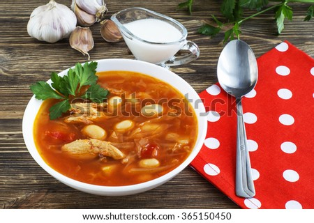 Traditional national Ukrainian beet soup borscht on the old wooden background. Red soup with beets, beans, cabbage, potatoes and meat. - stock photo