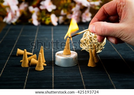 Traditional natural incense cones lighting with maches - stock photo
