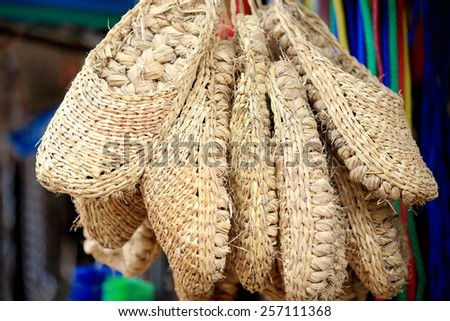 Traditional nepalese hempen shoes set for sale hanging at the entrance to a shop in the old city area. Panauti-Kavrepalanchok dstr.-Bagmati zone-Nepal. - stock photo