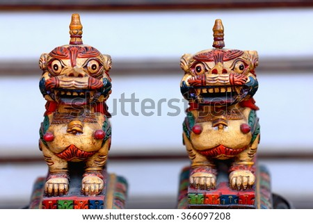 Traditional nepalese wooden carved snow lion figurines for sale in the windowshop of a souvenir store in the Thamel area-Kathmandu. Kathmandu district-Bagmati zone-Nepal. - stock photo