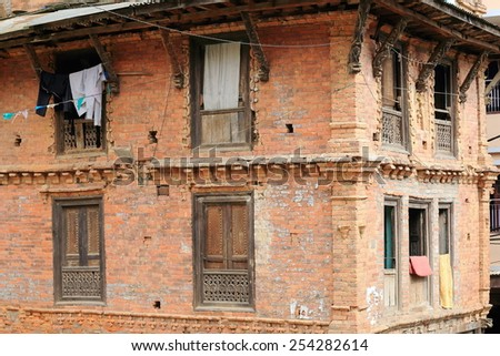 Traditional newar style red brick old house with carved wooden windowsills and roof struts-clothes hanging in the old city area. Dhulikhel-Kavrepalanchok distr.-Bagmati zone-Nepal. - stock photo
