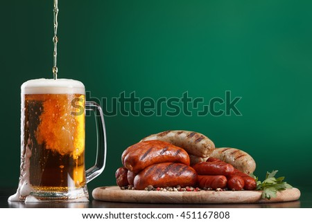Traditional Oktoberfest menu. Beer being poured into a glass with foam, traditional snacks, sausages grilled. With green background - stock photo