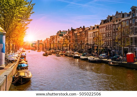 Traditional old buildings and and boats at the sunset in Amsterdam, Netherland
