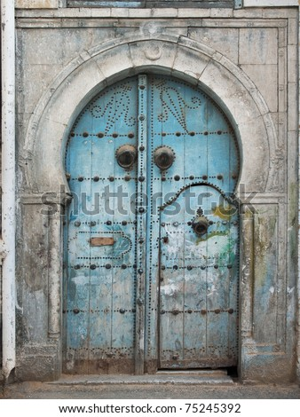 Traditional, old, damaged Tunisian front door - stock photo