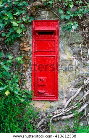 traditional old English red postbox mounted in stone wall surrounded by ivy. - stock photo