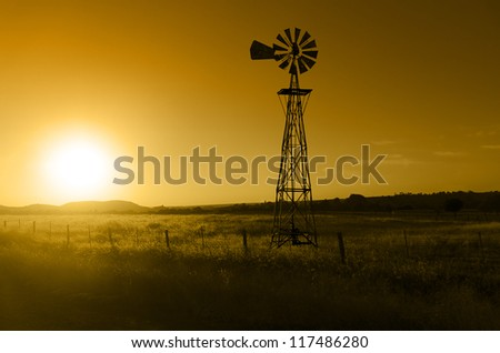 Traditional, old fashioned water pumping ranch windmill, range land, fencing.