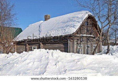 Traditional old log cabin covered with snow, snowdrifts, winter sunny day - stock photo