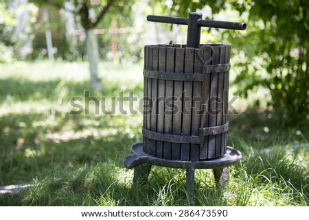 Traditional old technique of wine making, wooden antique grape press in tuscan countryside - stock photo