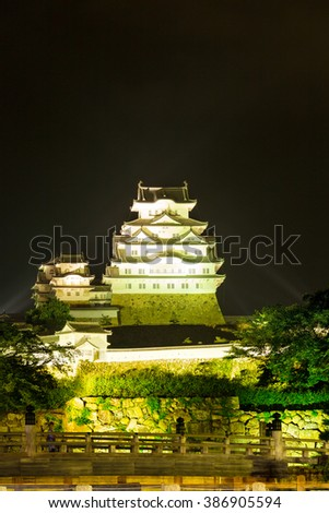 Traditional old wooden bridge, stone wall rampart at centered front of floodlight illuminated Himeji-jo castle at night in Himeji, Japan after 2015 renovations finished. Vertical