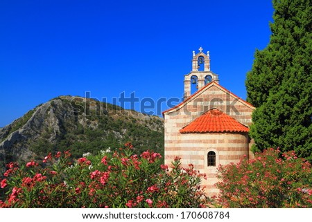 Traditional orthodox monastery surrounded by Mediterranean vegetation near the blue sea - stock photo