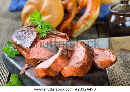 Traditional oven fresh Bavarian meat loaf on a wooden cutting board; rolls, pretzels and a mustard pot in the background