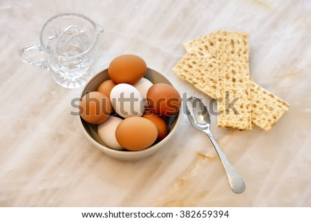 Traditional Passover eggs and salt water with matzoh sitting on natural Quartzite - stock photo