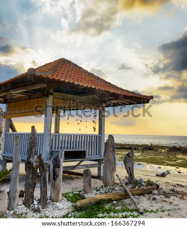 Traditional pavillion on sunset beach. - stock photo