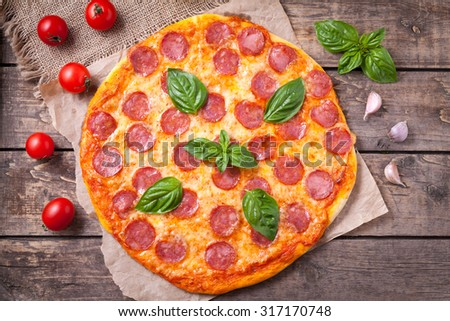 Traditional pepperoni pizza Italian delicious meal with salami, mozzarella cheese, tomatoes, basil and garlic on vintage wooden table background. Rustic style and natural light