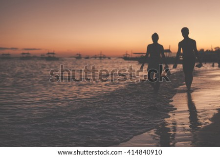 Traditional philippine boats floating in the sea and silhouettes of a woman and man walking along the sea shore during sunset. Panglao Island, Philippines. - stock photo