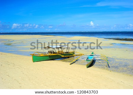 Traditional Philippines boats on the beach during the low tide on Shiargao island, Philippines