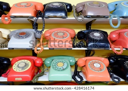 Traditional Phone many colors on wooden shelves. - stock photo