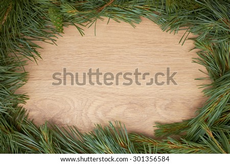 Traditional pine tree Christmas border decoration on a wood background. - stock photo