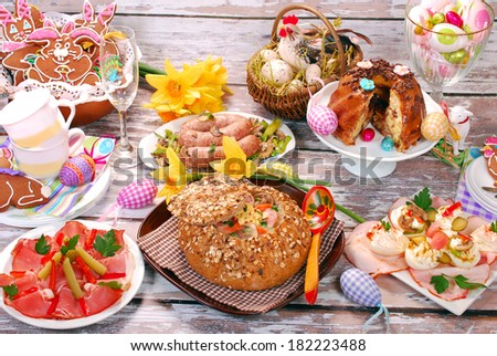 traditional polish dishes for easter dinner -white borscht (zurek) with sausage,egg and mushrooms in bread as bowl on old wooden table  - stock photo