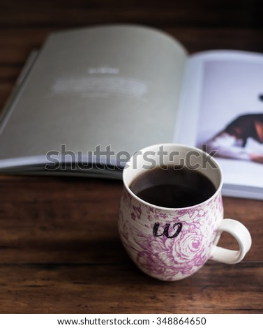 Traditional porcelain teacup with floral pink pattern on a wooden rustic brown table, selective focus