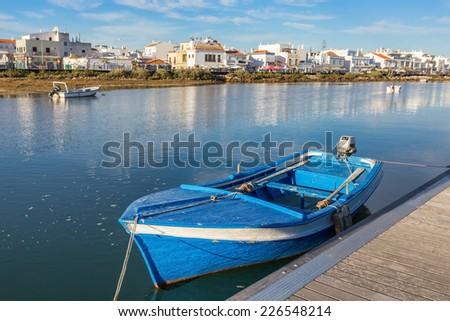 Traditional Portuguese boat at the dock. View Cabanas de Tavira. - stock photo