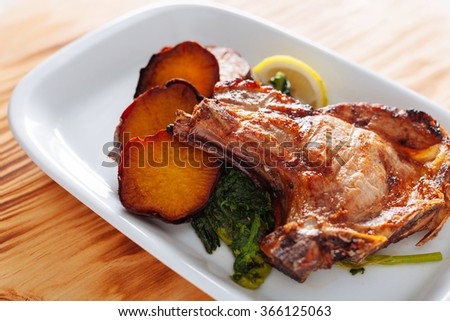 traditional Portuguese dish with grilled pork chops and sweet potato