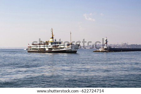 Traditional public ferry arriving to Kadikoy station in Istanbul. Water breaker is also in the view. Hagia Sophia and Blue Mosque are in the background.
