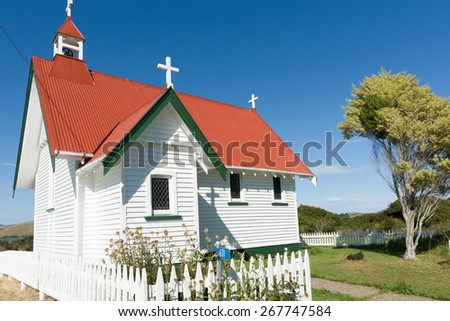 Traditional quaint wooden small christian church with white boards, red roof. St Mary's Anglican Church, Waikawa, in the Catlins area, of Otago, New Zealand. - stock photo