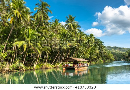 traditional raft boat on a jungle green river Loboc at Bohol island of Philippines - stock photo