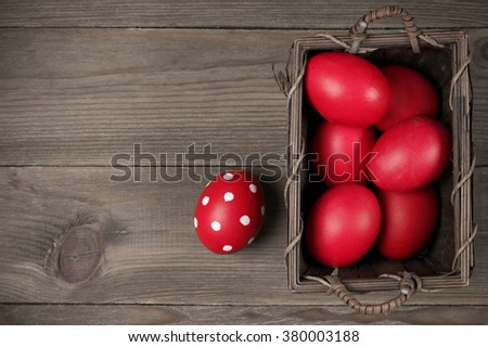Traditional red and dotted Easter eggs in basket on wood background. Top view point.