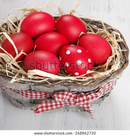 Traditional red and dotted Easter eggs in gray basket on rustic wood background. - stock photo