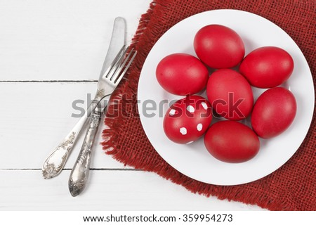 Traditional red and dotted Easter eggs in plate with napkin and silverware on white wood background. Top view point.