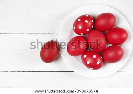 Traditional red and dotted Easter eggs in white plate on white wood background. Top view point. - stock photo