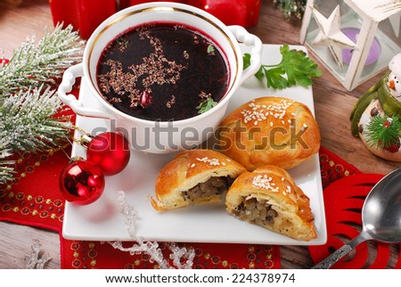 traditional red borscht in cup and yeast pastries stuffed with mushrooms for christmas eve supper - stock photo