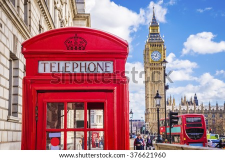 Traditional red british telephone box with Big Ben and Double Decker bus at the background on a sunny afternoon with blue sky and clouds - London, UK - stock photo