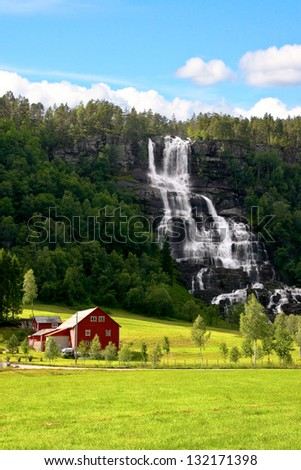 Traditional red farm next to a waterfall and green field in Norway. - stock photo