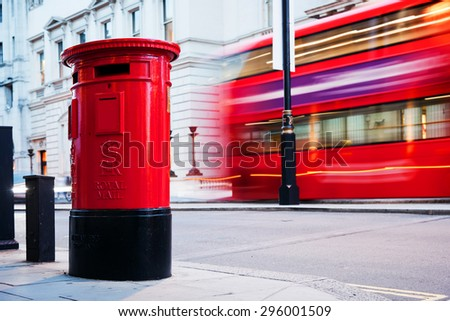 Traditional red mail letter box and red bus in motion in London, the UK. Symbols of the city and England
