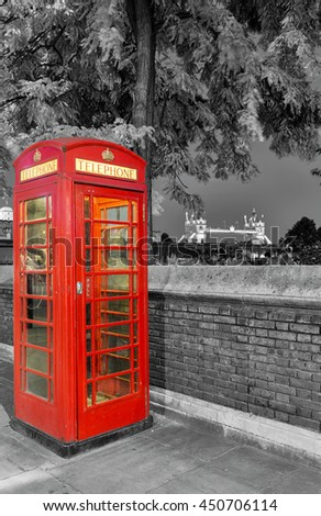 Traditional, red telephone booth in front of the Tower Bridge in London - stock photo