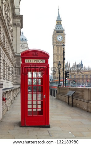 Traditional red telephone box in London public phone - a symbol of the city. Fragment of booths with the Big Ben in the background of the evening - stock photo