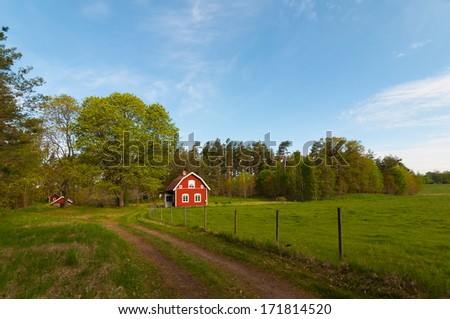 Traditional red wooden cottage in its environment in the swedish countryside in spring. Kalmar Laen (county), Sweden - stock photo