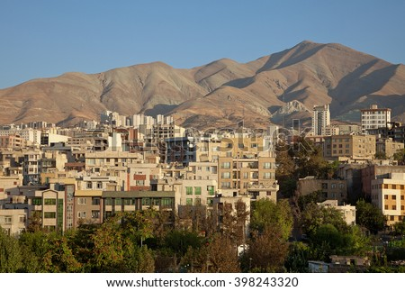 Traditional residential buildings in the skyline of Tehran between brown hills  and a row of greeneries on a clear sunny day. - stock photo