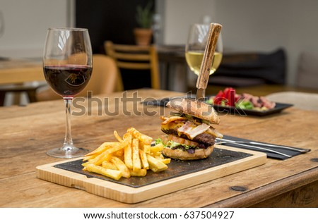 Traditional restaurant atmosphere with chips and a plate of tuna tataki with in the background on rustic wooden table and glass of red wine