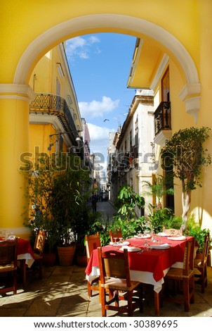 Traditional restaurant exterior with table settings on the terrace and view on old havana at caribbean island Cuba - stock photo