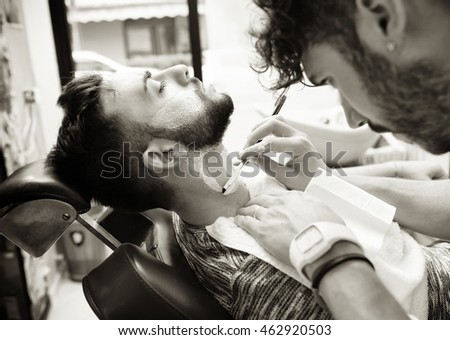 Traditional ritual of shaving the beard in a old style barber shop. Image with sepia filter.