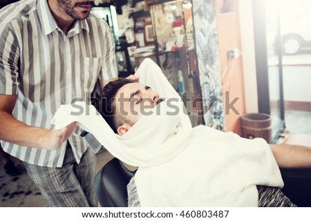 Traditional ritual of shaving the beard with hot and cold compresses in a old style barber shop.